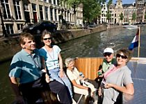 View five passengers enjoying a cruise down an Amsterdam canal