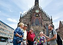 View a group of travelers in front of a beautiful fountain in Nuremberg Germany