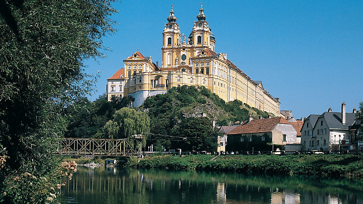 View some passengers aboard a boat enjoying a cruise down a river in Melk